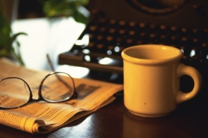 Typewriter, newspaper, glasses and a cup of coffee on desk, high angle view, close up